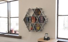 This geometric floating shelf by @rucheshelving looks like the strong, statement bookshelf you've been dreaming of, right? Right. Well, it's actually made of cardboard. The honeycomb shape and criss-crossing lines makes it super strong and able to hold your most precious books, and the chrome paint gives it the cool, sleek edge we love.