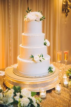 Love the simple elegance of this cake table. Gold sequin linen with bling cake stand and the fresh ivory flowers on ivory buttercream.   REAL WEDDING :: LOGAN + WILLIAM {Southern Romance} http://www.neworleansweddingsmagazine.com/real-wedding-logan-william-southern-romance/  photo: Sonia Savio | location: Southern Oaks Plantation | Cake: Frosted Fantasies by Nikki | Florals: Poppy and Mint