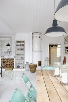 Pale aqua chairs add an unexpected and beautiful punch of colour to the purity of this Scandinavian beach house.