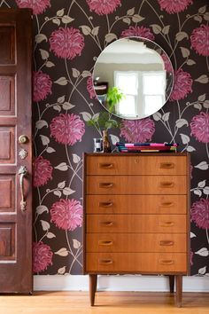 dresser in entryway with floral wallpaper and circular mirror