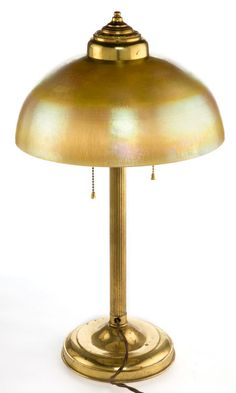 TIFFANY STUDIOS FAVRILE GLASS SHADE WITH BRASS LAMP BASE  Gold Favrile glass domed shade with associated two-light brass lamp  base, circa 1920  Engraved: LCT, Favrile  21-3/4 inches high (55.2 cm)           Estimate: USD 2,000 - USD 4,000.