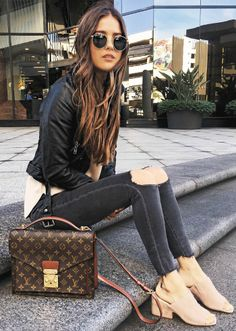 Paola Alberdi + black skinny jeans + ripped at the knee + classic edge + we all crave + leather jacket + light clog style sandals + authentic + spring style.   Bag: Louis Vuitton.