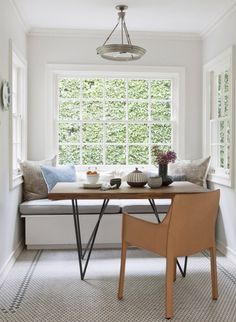 Bright and airy breakfast nook with wood table and leather armchair