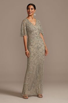 This stunning V-neck gown features a mesh overlay embellished with intricate beadwork and sequins. Illusion flutter sleeves finish the look, giving the dress a capelet-inspired appearance. Mob Dresses, Necklines For Dresses, Event Dresses, Formal Dresses, Mother Of The Groom Gowns, Mother Of Bride Outfits, Mother Of The Bride Dresses Long Sleeve, Mother Of The Bride Fashion, Long Mothers Dress