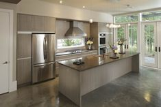 Monochromatic kitchen, Custom cabinetry, quartz countertop, stainless steel appliances and sealed concrete floors
