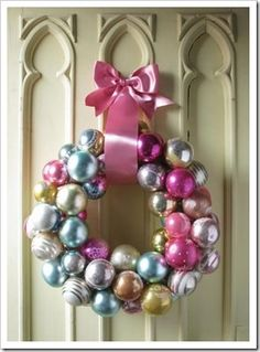 wreath  - coat hanger bent into circle  - glue tops on of ornaments onto ornament  - string ornaments on circle, alternating sizes  - voila! I have one in Christmas color brights--love this pink twist!