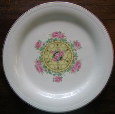 """Sweet 1920's vintage USA made cream colored decorative plate with nice medallion center of pink roses.  9.25"""" is on the small size of large decorative plates. Very art deco in feel with a yellow and black medallion surround by pink roses and green leave. Warranted 22K gold edge trim Decorative plate made in USA. Round shaped cream colored decorative plate with yellow, pink, green and black design. Plate is a bit shabby with glaze crazing and some wear. It's old!"""