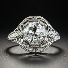 A gorgeous bright white and brilliant European-cut diamond, weighing 2.02 carats,sparkles solo from within an exceptional and highly distinctive solitaire mounting, crisply die-struck and hand finished in platinum during the peak of the period - circa 1925. The 'cigar band' shape ring is elegantly pierced with a light and lacy open design hand finished with delicate milgraining and hand engraving. Singular, chic, sophisticated, and stunning! Currently ring size 6 1/4.