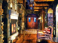Handsome wooden doors open to reveal a pinwheel-tile floor that fans out in a traditional pattern. Steps away hangs a rustic swing from La Lune Collection accented with pillows made of fabric inspired by classic Swiss chalet motifs. The stone fireplace is an enormous three-sided structure that anchors the dining room, kitchen and great room. PHOTO BY Gibeon Photography