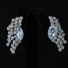 Unusual earrings by Coro have a large marquise-shaped rhinestone and a rhinestone-chain fringe along the outer edge. These are ear climbers that follow the outer curve of your ear so you sparkle with every move. They're light blue and silvertone, with ...