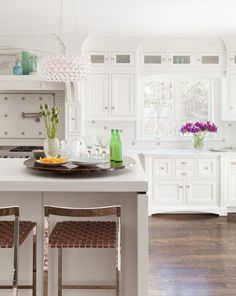 Acrylic light fixture is the perfect addition to this white kitchen