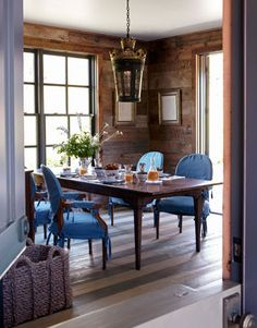 love the blue slipcovered chairs and the wood paneling. Also the brightness from the windows.