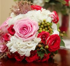 white hydrangea, pink roses, green hypericum, and light pink astilbe