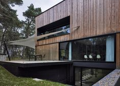 Timber-clad house with textured concrete interior by Ultra Architects