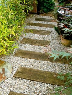 Cut sleepers have been laid among pebbles to give a beach look to pathway. Soft surfacing for garden pathways consists of natural materials that include combinations of stone, wood and shell.
