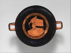 Terracotta kylix (drinking cup). Classical. ca. 480–470 B.C. Greek, Attic. Thracian woman. The large piece of patterned cloth used as a shield identifies the figure as Thracian. She hastens forward holding a spear in her right hand. The characterization suggests that she is an excerpt from a larger scene depicting the death of Orpheus, the irresistible musician.