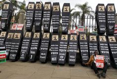 An activist sits next to mock coffins outside the Kenyan parliament in Nairobi during a protest organized by the 'Kenya Ni Kwetu' lobby group, against what they call a culture of impunity by the members of parliament. (Reuters)