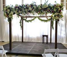 Serene Chuppah simple wooden structure decorated with front-heavy floral design and back garland accent to give depth