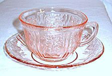 These are Depression Glass cup and saucer sets in the Sharon or Cabbage Rose pattern made by Federal. The color is pink and they are in excellent condition with no chips or cracks.