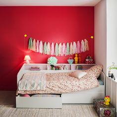 Une chambre d'enfant avec un mur plein de peps. Un mur couleur rouge cerise pour la vitalité, une guirlande pastel pour le coté original assortie à une jolie parure de lit couverte de pois multicolores et un coffre bohème pour enfermer les petits secrets, autant de bonnes idées à copier pour une chambre d'enfant réussie !