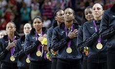 Members of the U.S. women's basketball team stand for the national anthem after receiving their gold medals following their win over France in the gold medal basketball game.