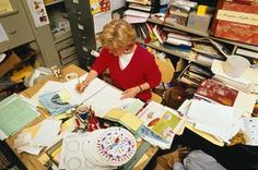 Primary school teacher working at crowded desk in cramped office - Bruce Forster/The Image Bank/Getty Images