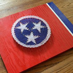 The Tennessee state flag string art by Herring Design Co. highlights the tri-star emblem displayed on the flag. It's the perfect piece to represent your Tennessee pride! Every piece is unique due to t