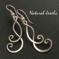 Earrings totally handcrafted from 925 STerling silver wire.      Two fragile tendrils of silver, filling up the gaps in each other and grown to perfec