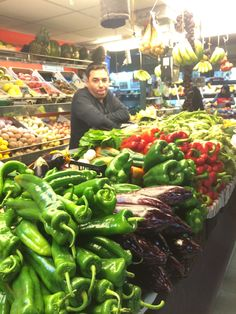En el mercado, hay muchas verduras de muchas colores. Tambien hay un vendedor y él parece aburrido.