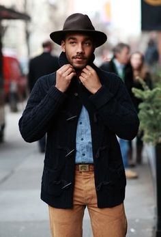 A deep blue toggle cardigan and brown chinos will convey a carefree easy vibe.  Shop this look for $132:  http://lookastic.com/men/looks/hat-denim-shirt-duffle-cardigan-belt-chinos/4939  — Dark Brown Wool Hat  — Light Blue Denim Shirt  — Navy Duffle Cardigan  — Brown Leather Belt  — Brown Chinos