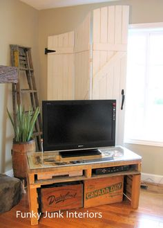 New TV stand made from a pallet.  The milk and soda crates underneath? They're DVD storage bins!  Love this!!