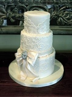 All white lace wedding cake with bow