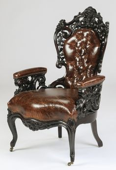 Victorian Rococo Revival armchair, in the manner of John Henry Belter, 19th century, executed in mahogany with embossed and button-tufted leather upholstery, the crest carved with grapevine motif, the nailbacked seat rail carved with scrolled flourishes, the whole raised on cabriole legs