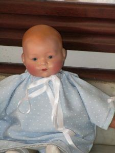 Antique bisque head (porcelain) baby with clothing body. The hands are celluloid and original.The Heubach 349/12/0 brand is on the nape of the neck.