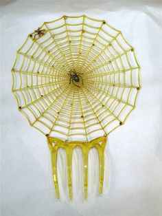 A French hair comb, 1900-20, portraying a spider at the centre of its web about to devour a fly; a symbol of predation. (Gallery 47/collectorsnet)