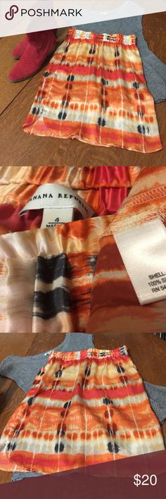 """Banana Republic skirt silk orange blue red cream 2 NWT Elastic waist w/ side pockets multicolored skirt is 100% silk and beautiful.  It's a very small size 4 and the silk has no give so would fit 2 or 0 better.  Waist 14"""" length 21"""".  Beautiful orange cream, navy, burgundy and gold.  I really wish it fit!!!  Gray AE top is also for sale in my closet. (I'm keeping my red boots! 😍) Banana Republic Skirts Midi"""
