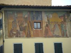 Fresco on building facade in Florence depicting historical and modern times. mercatoantiques.com