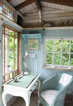 A pretty little rustic home office done in a lovely shade of blue. It look likes it has a wonderful view too.