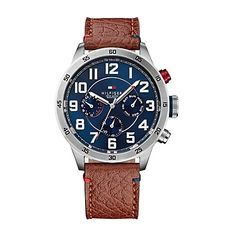 Tommy Hilfiger men's watch. Mountain time, Pacific time, anytime our bold chronograph makes an impression wherever you roam. Styled in stainless steel with a trio of subdials, the blue face stands out simply and stylishly with a vachetta leather strap and tachymeter to measure distance based on speed. <br>• Stainless steel case with brown leather strap.<br>• 46mm case, 3-hand movement, microflag. <br>• Water resistant up to 50 meters.<br>• 10-yr limited warranty.<br>• Imported.<br><br>