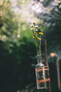 Clearly define your outdoor party space with flowers arrangements on sticks - image via Sycamore Street Press