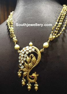 22 carat gold antique finish gundla mala with beautiful designer peacock pendant studded with polki diamonds and ruby. Related PostsAntique Gold Necklace with Peacock PendantAntique Gold Long Chain with Peacock PendantLayered Diamond Necklace and Antique Necklace SetsPeacock Pachi PendantsAntique Gold Necklace and Haram SetBeads Mala with Peacock Pendant