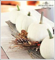 White pumpkins, an old board, and a decorated twig wreath for a centerpiece.