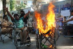 Disabled protesters set a wheelchair on fire during demonstrations against social welfare cuts and demand special job quotas during International Disability Day. Hyderabad, Pakistan. 3rd December 2011