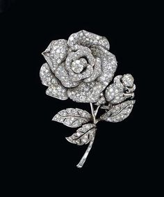 A DIAMOND BROOCH Designed as a pavé-set diamond rose, extending a rectangular-cut diamond stem and pavé-set diamond leaves and bud, accented by two old European-cut diamonds, mounted in platinum Diamond Brooch, Diamond Jewelry, Modern Jewelry, Fine Jewelry, Jewellery, Antique Jewelry, Vintage Jewelry, European Cut Diamonds, Bridal Necklace