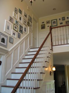 photo wall on the staircase - I really want to do this!  Love the blue, white and grey frames!