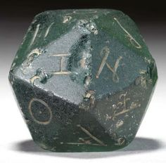 A ROMAN GLASS GAMING DIE: Circa 2nd Century A.D. Deep blue-green in color, the large twenty-sided die incised with a distinct symbol on each of its faces. 2 1/16 in. (5.2 cm.) wide.