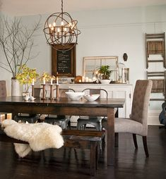 The dream dining room is all about mismatched chairs, candles, and elegant touches like the mirrored tray on the cabinet or the brass chandelier.