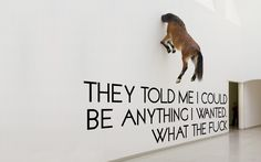 Installation by Maurizio Cattelan with text added by an anonymous artist
