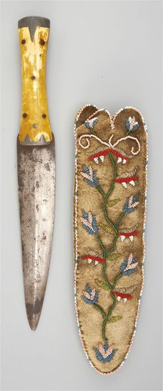 """Plains Cree beaded buffalo-hide knife sheath, ca.1850. Decorated on the front with a floral design, finely stitched in various shades of opaque and translucent beads; a bone and lead-handled dagger enclosed, L: 11"""""""