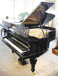 An 1895 Bluthner grand piano with a polished, black case and ornate music desk.  #bluthner